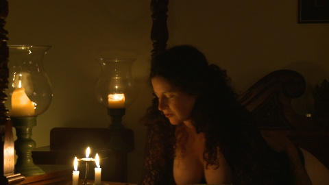 Woman by candlelight on bed